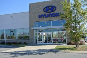 A close-up view of a local Hyundai dealership. Interior lights are visible through their transparent facade.