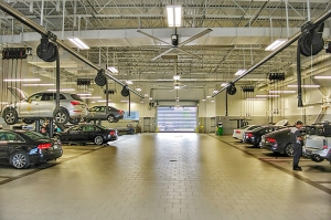 The commercial lighting upgrade at this car dealership's service area helps mechanics work productively and safely.